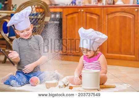 Party time: boy and girl in chef's hats sitting on the kitchen floor soiled with flour playing with food making mess and having fun