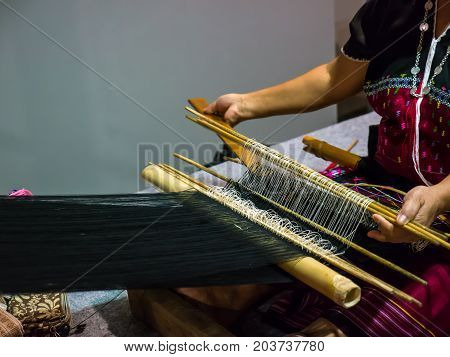 Woman is making handicraft work with local loom