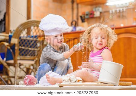 Two cutest kids boy and girl in chef's hats sitting on the floor soiled with flour, playing with food