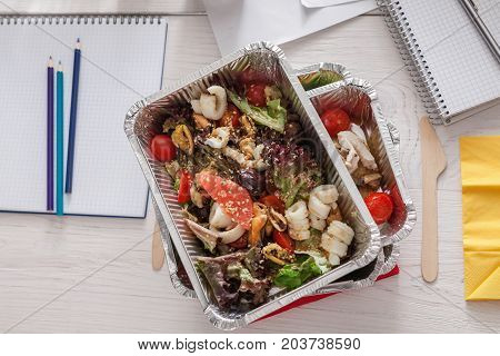 Healthy daily meals delivery at office table, coffee take away cup and vegetable salads in foil containers on white wooden desk. Snack at break time