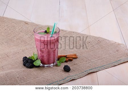 A composition of a transparent glass full of blended smoothie from berries with a straw on a bag and on a wooden background. A few ripe, natural blackberries, mint, and cinnamon sticks on a desk.