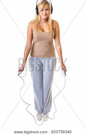 Fitness slimming loosing weight concept. Happy blonde woman jumping on skipping rope wearing big headphones and sportswear.