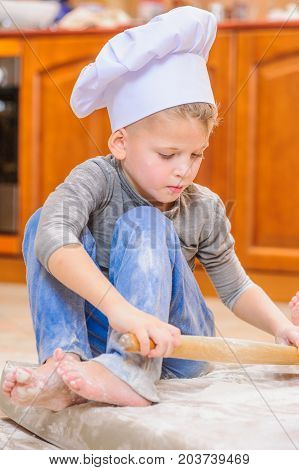 Two Siblings - Boy And Girl - In Chef's Hats Sitting On The Kitchen Floor Soiled With Flour, Playing