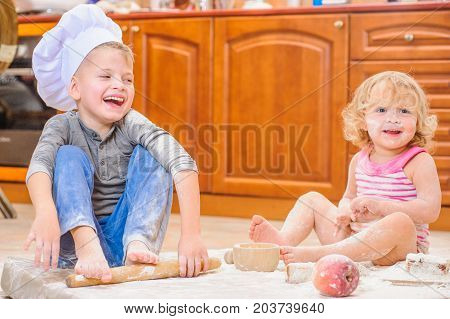 Cutest  boy and girl in chef's hats sitting on the floor soiled with flour, playing with food