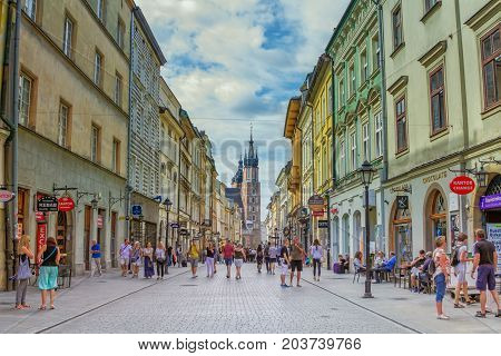 Krakow/Poland- August 15, 2017:Cityscape of old town, tourists and citizens walking on Florianska street, view of town hall on background, sunny summer day with blue sky