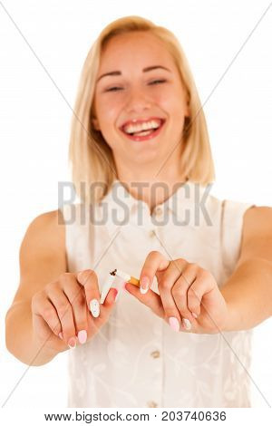 Attractive young woman breaking a cigarette as a gesture for quit smoking