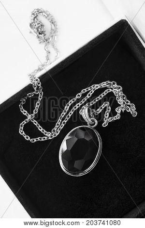 Vintage black crystal medallion in black jewel box closeup