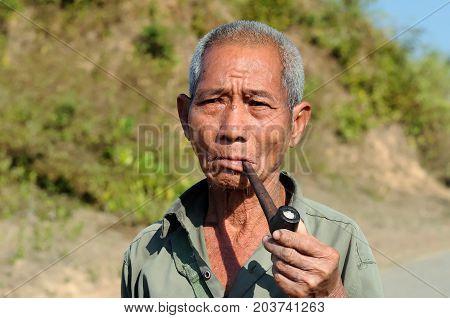 BAGAN MYANMAR - 24 JANUARY 2011: Portrait of the Burmese smoking a pipe