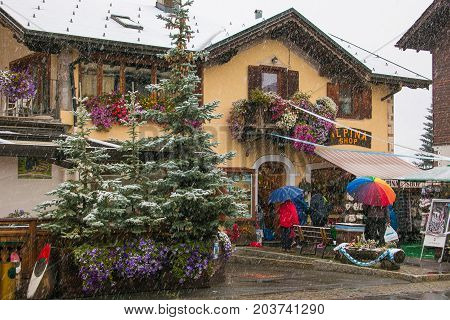 LIVIGNO, ITALY - SEPTEMBER 10, 2017: Tourists shopping on the streets of duty-free area in Livigno during snowy day