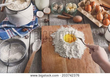 Stir dough. Flour, milk, butter, yeast, spices and eggs carton on rustic wooden table, cooking ingredients. Female chef baker pov