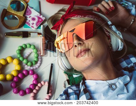 Closeup portrait of blonde with headphones and sunglasses, rests on the floor listening to music. The mess in the room. Modern women's style.