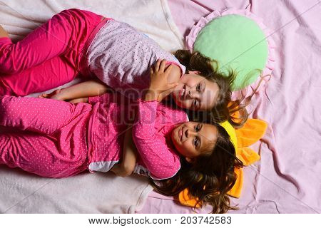 Girls Lie On White And Pink Bed Sheets Hugging