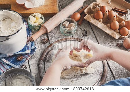 Baking concept. Flour, milk, butter, yeast and eggs carton on rustic wooden table, cooking ingredients. Unrecognizable woman's hands pov view knead dough. Female chef