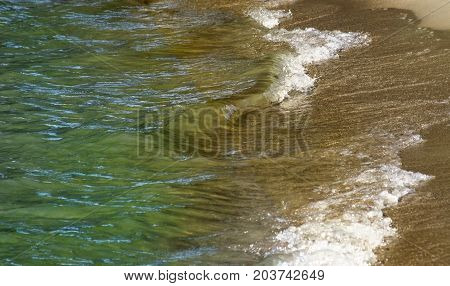 Soft waves in shades of green and brown rolling up to Shoreline