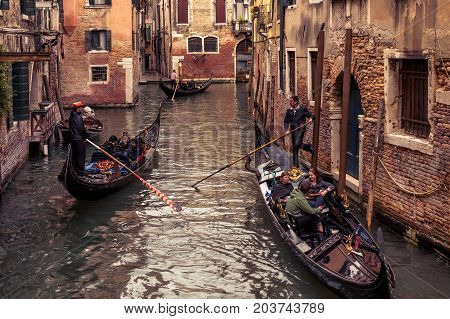 Venice, Italy - May 20, 2017: Gondolas with tourists floats along the old narrow street. Gondola is the most attractive tourist transport in Venice.