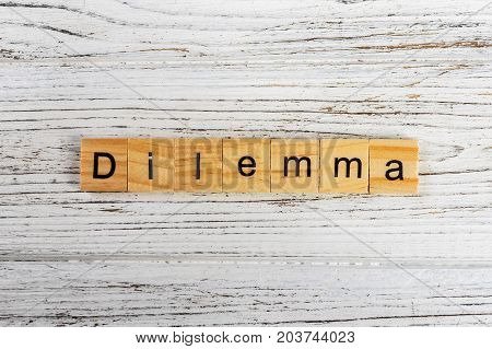 DILEMMA word made with wooden blocks concept