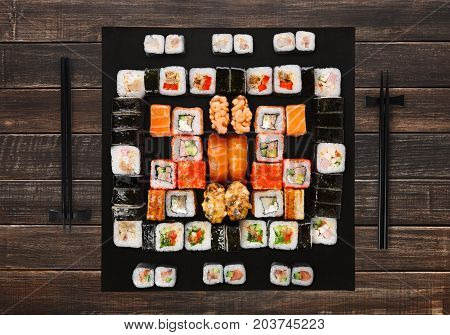 Japanese food restaurant delivery - sushi maki, unagi, gunkan and roll big party platter set on brown wood background, above view