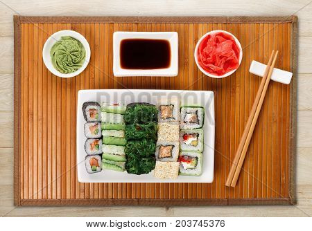 Japanese food restaurant delivery - sushi maki, unagi and roll platter set on mat on natural wooden background, above view