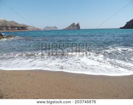 playa con oleaje e isla al fondo