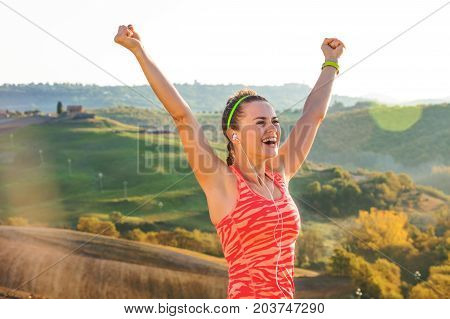 Smiling Sportswoman Against Scenery Of Tuscany Rejoicing