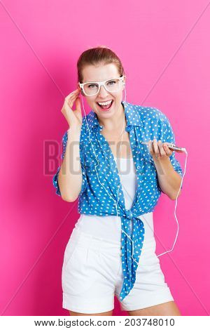 Happy young woman with earbuds on a pink background