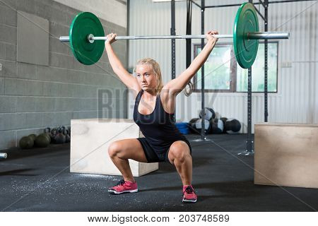 Full length of determined young woman lifting weights in health club