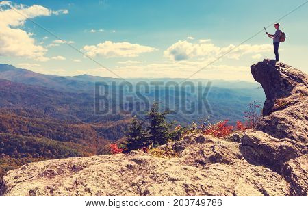Man with a map at the edge of a cliff overlooking the mountains below