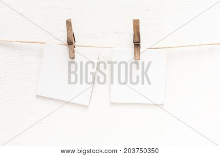White blank cards on rope, light wall background. Creative reminder, small sheets of paper on old clothespin, memo backdrop