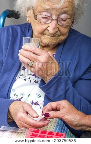 Senior Citizen taking Pill. A senior citizen, in a wheelchair, being given her medication by a carer.