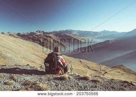 Male Hiker Relaxing At Sunset At The Mountain Summit And Looking At Majestic Panorama Of The Italian