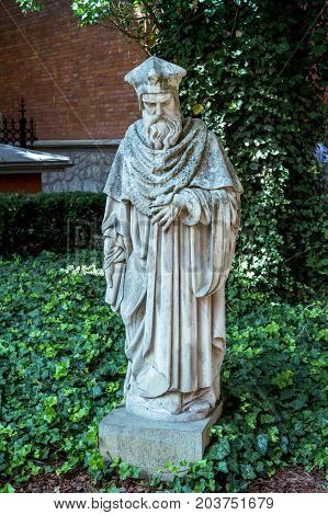Krakow/Poland- August 15, 2017: stone statue at Professors Garden of the Jagiellonian University with overgrown ivy on the ground