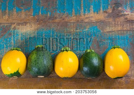 Round Green And Yellow Courgette Or Zucchini, On Wooden Background, Close Up
