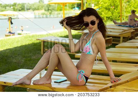 beautiful glamorous slender Lady posing on camera in a bathing suit on a beach Lounger