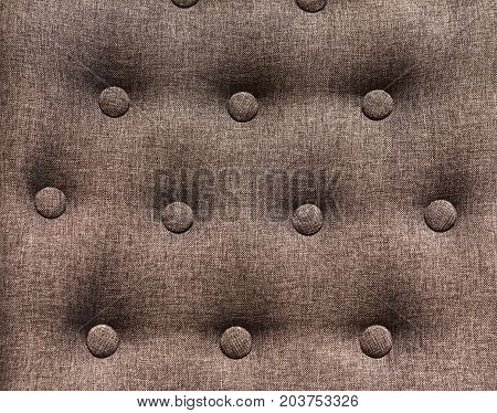 Chesterfield styled furniture with buttons close up. Decorated sofa back background