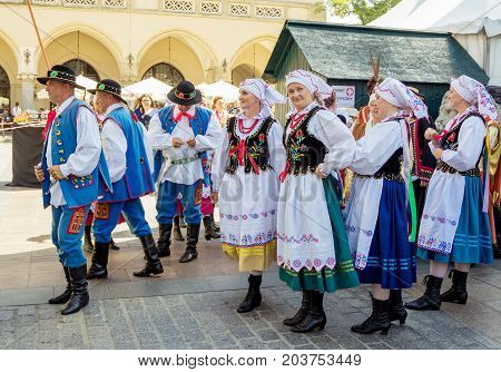Krakow/Poland- August 15, 2017: dancing group - men and women, wearing traditional clothes, waiting for the beginning of performance, on celebration of Polish Armed Forces Day at main Market Square