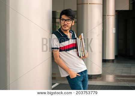 cute young guy in a t-shirt stands on the street and keeps on hand book