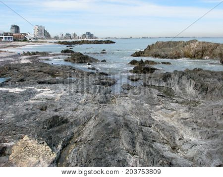 FROM BLOUBURG STRAND, CAPE TOWN SOUTH AFRICA, WITH RUGGED ROCK FORMATION IN THE FORE GROUND AND HIGH RISE BUILDINGS IN THE BACK GROUND