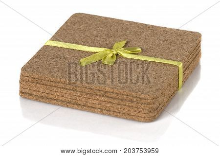 cork coasters under glasses on a white background