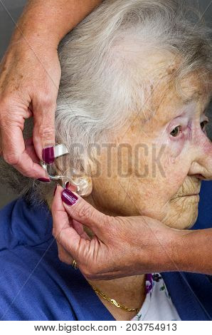 Senior Citizen and Hearing Aid A carer fitting a senior ladies hearing aid.