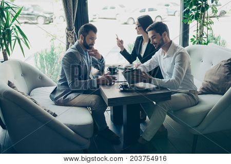 Business Negotiation In A Cafe. Three Partners Are Discussing The Contract. Young Bearded Attractive