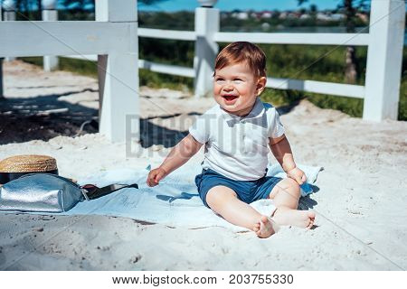 Little baby boy sitting on the sand, kid playing with sand