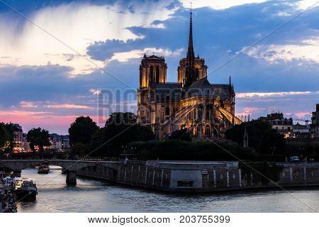 View of southern facade of Notre Dame de Paris from the Seine River at night. Notre Dame Cathedral is a medieval catholic cathedral and finest example of french gothic architecture. Paris France