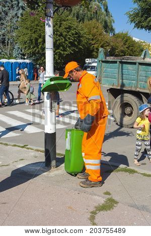 The utility worker removes garbage from the full tank. Day of the city. Zhitomir of the year 1133. September 2017 Ukraine.