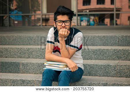 young brooding guy sits on the stairs keeps books and looks ahead