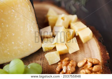 Cheese platter, parmesan on natural wood disc, whole piece and diced cheese with grapes and nuts, still life, copy space, closeup, background