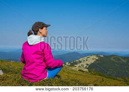 Proud woman traveler in bright colorful jacket is sitting on alpine meadow among green grass on the background of panorama mountains in blue haze and looking into the distance.