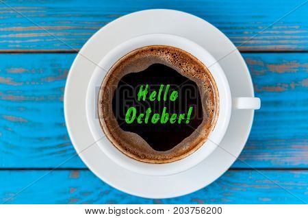 Hello October on morning coffee cup at blue wooden home table. morning background.