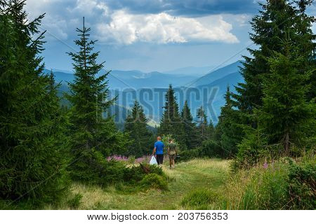 Two travelers walk along the alpine meadow between huge pines with bowlers and bottles of water to the camp on the background of mountain panorama. Epic adventure in the mountains.