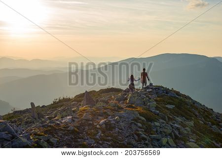Teenagers boy and a girl walk along a stony mountain range to the setting sun. Amazing travel in the wilderness. Back light back view.