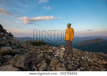 Satisfied traveler stands on top of the mountain against the background of the panorama of the mountains looking out into the distance admiring the amazing sunset. Wide angle.